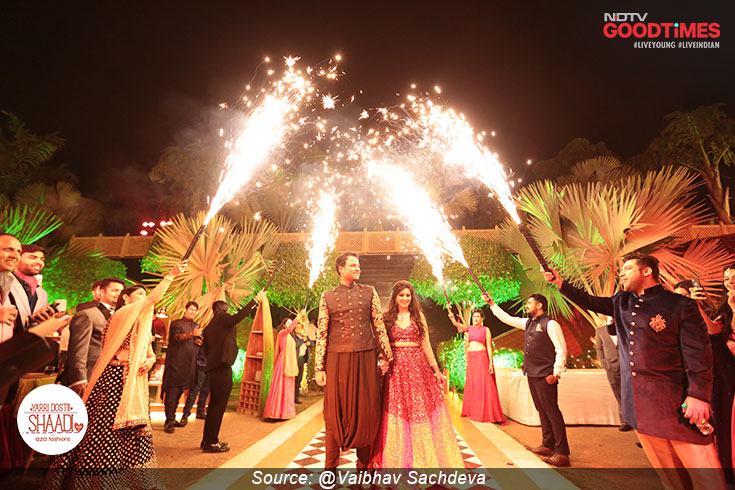 A picture perfect sangeet entry, Mukul and Sonika walk towards the stage with fireworks lighting up the way
