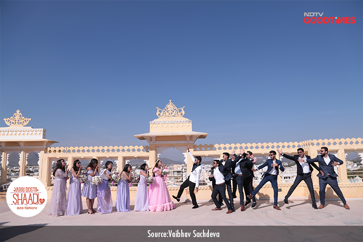 Anvita and Ankit strike a pose with their gang of family and friends against the picturesque backdrop of a palace in Udaipur.