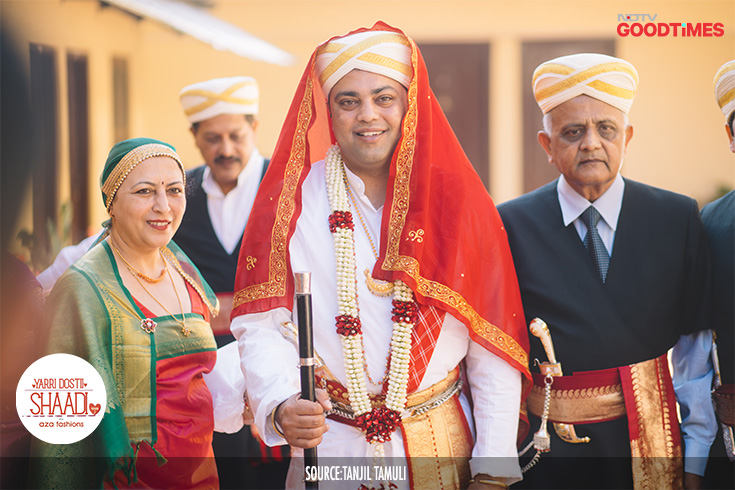 Our groom, Vikram too gets dressed the traditional way. Wearing a white long-sleeved Kupya, a red Chele or stole around his waist and a white and gold turban covered with a veil, he is all set to bring the baraat to the mandap.