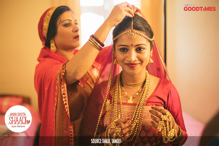 Jahnavi is dressed to the nines, in a red silk sari draped in the Kodava style, a long-sleeved blouse and a red veil. She is bejewelled with traditional Kodava gold ornaments like the Pathak, Jomale, Kokkethathi & Gund, Kadagas, Pimbale, Jhumkis and silver jewellery for her feet.
